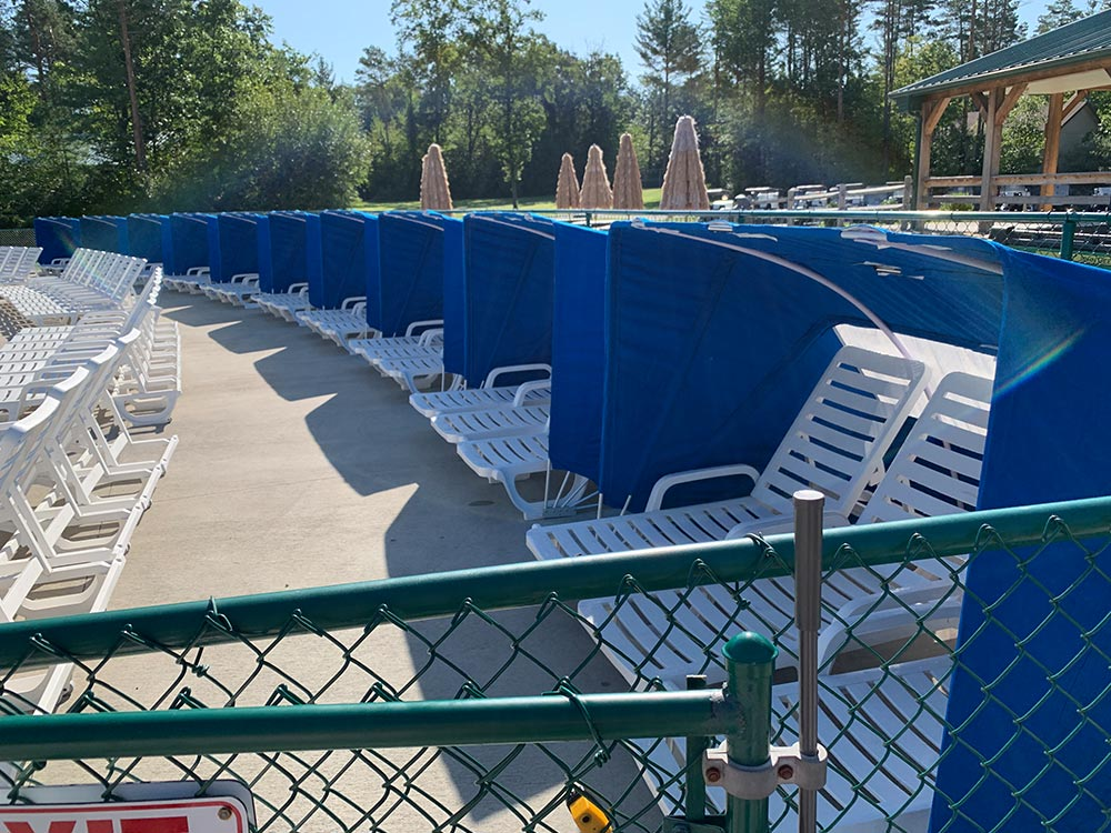 shaded poolside chairs at Moose Hillock RV Park in Lake George