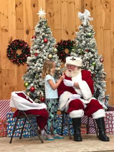 Girl getting candy cane from santa