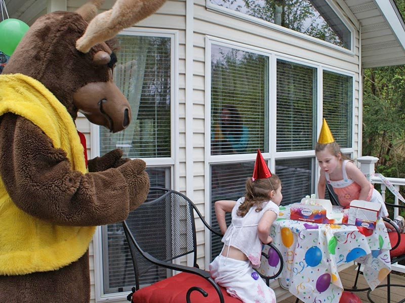 Bruce the moose at a birthday party with 2 girls blowing out candles on cake
