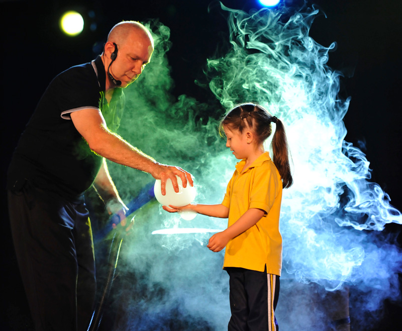 Performer giving young girl bubble of smoke