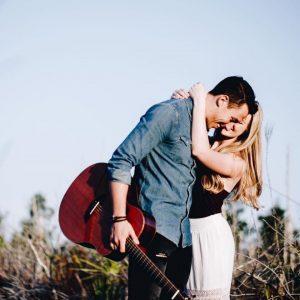 Women hugging man with guitar