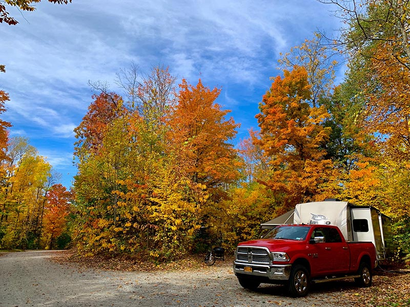 Fall foliage surrounding campsite with red pickup truck and RV trailer