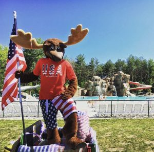 moose hillock mascot in front of large swimming pool at moose hillock resort in lake george ny