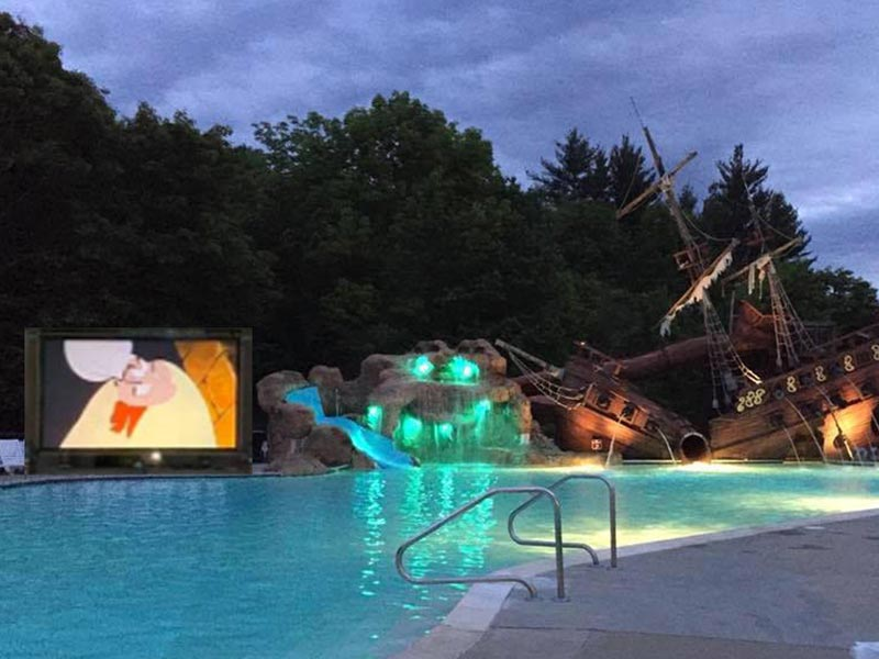 Movie screen next to pool