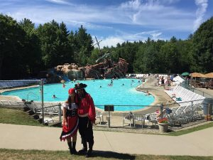 2 people dressed up as pirates in front of pool