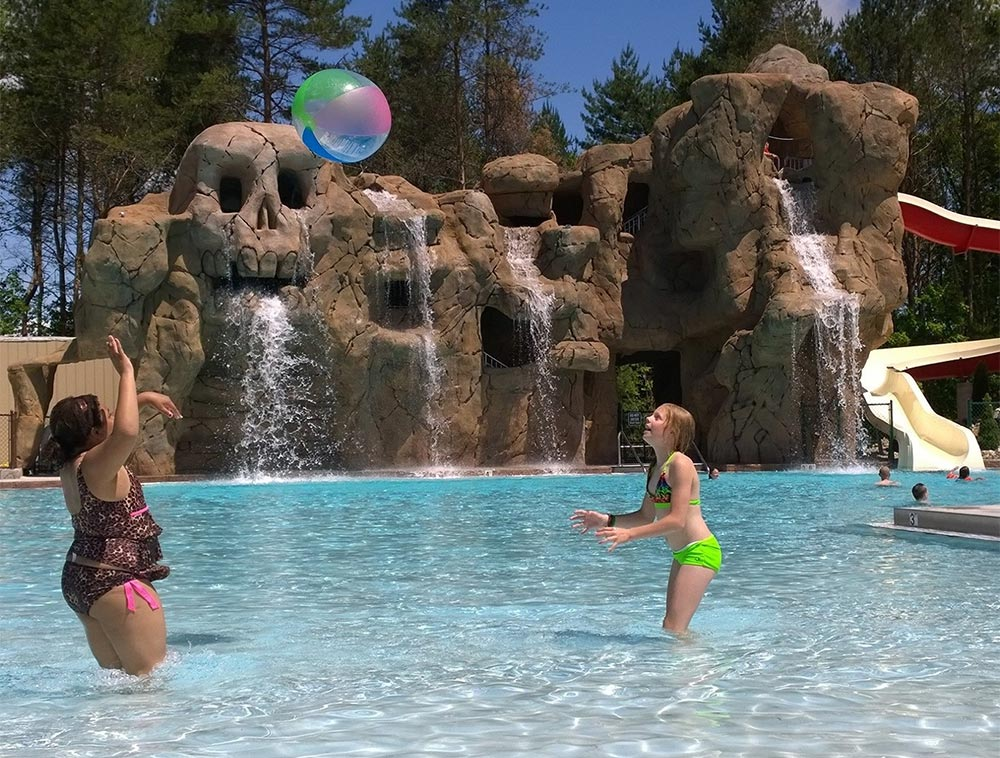 Kids playing with beach ball in pool