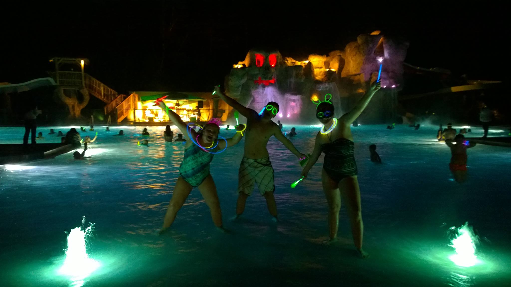 Kids in pool with glow sticks at night