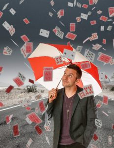 Man with umbrella protecting himself from cards
